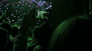Girl taking photo with smartphone in the club at the concert, 4k