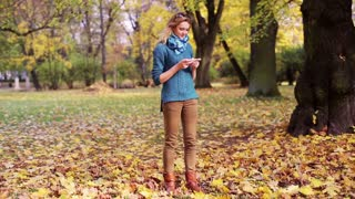 Girl texting on smartphone in the park and smiling to the camera