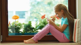 Girl using cellphone. Child sitting on the windowsill and playing in smartphone and laughing. Zooming