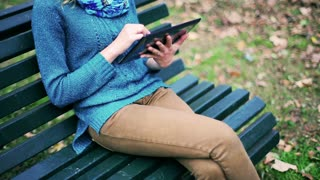 Girl using tablet in the park and sitting on the bench