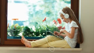 Girl using tablet pc. The child sitting on a window sill against the flower and smiling. Zooming