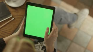 Girl Using Tablet with Green Screen. Over the Shoulder View