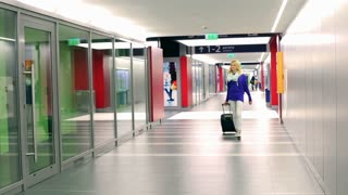 Girl walking and smiling to the camera on corridor