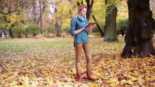 Girl walking and using tablet in the park