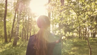 Girl walking in the magnificent forest while relaxing from the city. Elegant woman enjoying nature with bright sunlight shining through the trees.
