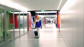 Girl walking on corridor and pulling suitcase