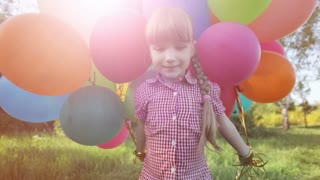 Girl walking with balloons in the park and looking at camera. Lens flare and sunlight