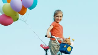 Girl waving hand at camera. She holds a bicycle with balloons. In the basket there are bread and milk