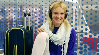 Girl wearing headphones and smiling to the camera on the station