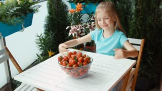 Girl with a big plate of strawberries looking at camera and smiling. Zooming