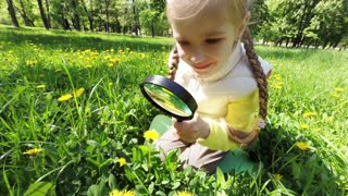 Girl with magnifying glass looking at dandelions