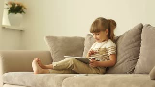 Girl with tablet sitting on sofa and laughing