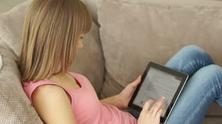 Girl with the tablet pc is sitting on her couch