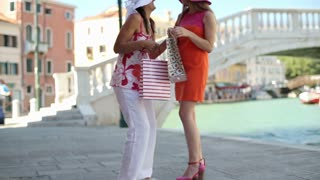 Girlfriends talk after shopping by canal
