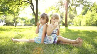 Girls eating ice cream. Sitting on the grass