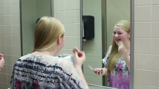 Girls Putting on Makeup in School Bathroom