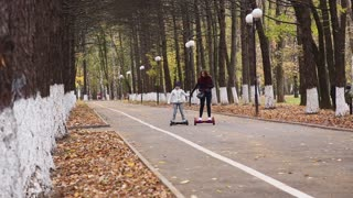 Girls riding electric gyro scooter in autumn Park