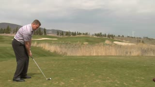 Golfer Hits Ball With Iron Windmill In Distance