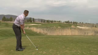 Golfer Hits Ball With Iron