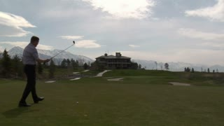 Golfer Lines Upshot With Clubhouse And Snowy Mountains In Distance