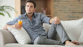 Good-looking guy sitting on couch and drinking juice