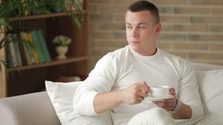 Good-looking guy sitting on sofa holding cup of tea and smiling