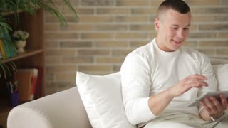 Good-looking guy sitting on sofa with touchpad and looking at camera with smile