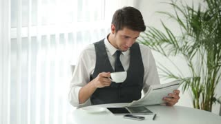 Good-looking man sitting at table drinking coffee and reading newspaper