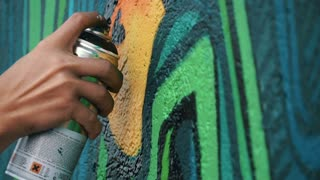 Graffiti artist drawing on the wall, close up