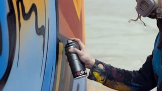 Graffiti artist painting on the wall, close up, slow motion, interior