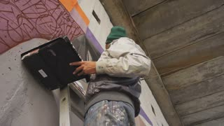 graffiti artist painting on the wall, steadycome shot