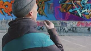 Graffiti artist watching at his work and smoking