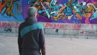 Graffiti artist watching at his work
