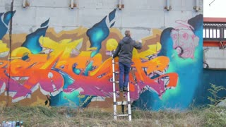 Graffiti artists painting on the wall, exterior