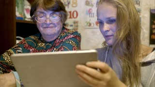Grandmother and granddaughter looking through the photos using tablet computer. They talking and smiling
