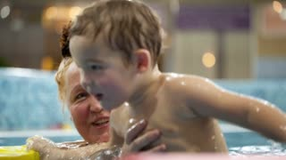 Grandmother helping her grandson to jump in the swimming pool, boy holding floatation devices