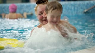 Grandmother holding her grandson having fun in the swimming pool