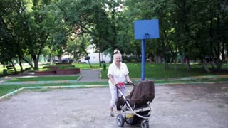 Grandmother walks with her grandson in a baby stroller in the yard. Camera motion. Wide shot.