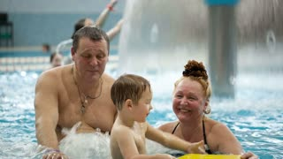 Grandparents watching their grandson having fun in the swimming pool