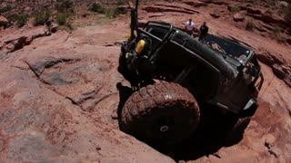 Green jeep struggling to drive over huge rocks 12