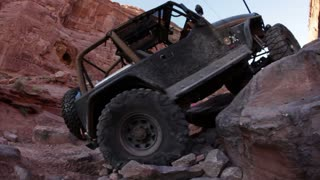Green jeep struggling to drive over huge rocks 15