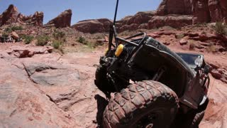 Green jeep struggling to drive over huge rocks 1