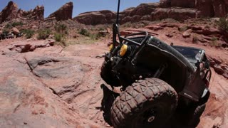 Green jeep struggling to drive over huge rocks 6