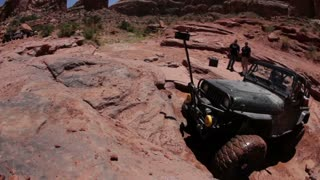 Green jeep struggling to drive over huge rocks 9