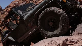 Green jeep tires driving on rocks