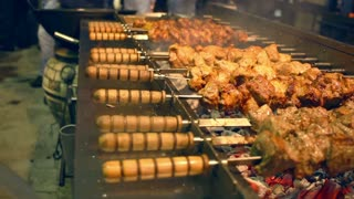 Grilled meat on skewers. Street food. Meat rotating on skewer. Food grilling on barbecue. Preparing tasty meat barbeque on skewers. Shashlik grill over coals. Grilled meat shashlik. Shish kebab.