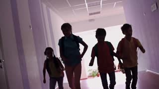 Group of elementary students running along dark hallway in slow-mo
