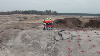Group of engineers talk on construction site near explosives works area aerial top shot
