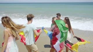 Group of Friends Carrying Flags on Sunny Beach