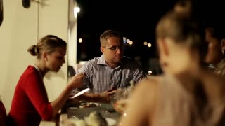 Group of friends celebrating dinner on the terrace at night, steadycam shot